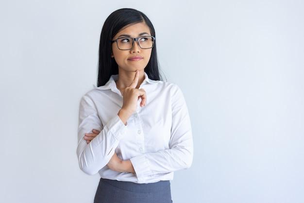 Menina de escritório chinesa pensativa que estuda a informação nova Foto gratuita