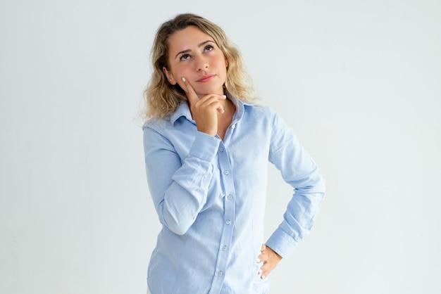 Menina de escritório pensativa pensando sobre sua ideia Foto gratuita
