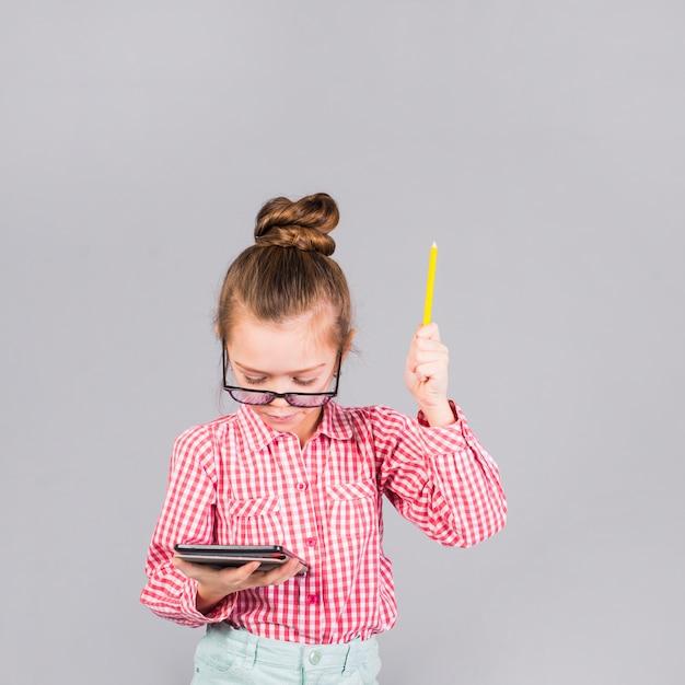 Menina de óculos com caneta usando tablet Foto gratuita