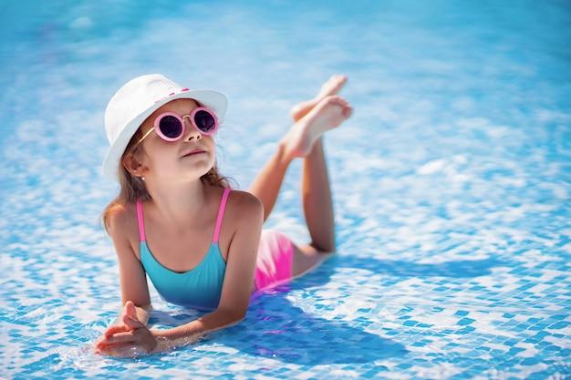 Menina de óculos escuros e chapéu com unicórnio na piscina do resort de luxo nas férias de verão na ilha de praia tropical Foto Premium