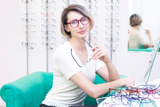 Menina de óculos para a visão. tentando óculos Foto Premium