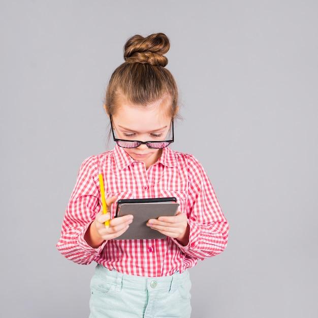 Menina de óculos usando tablet Foto gratuita