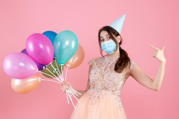 Menina de olhos arregalados com boné de festa segurando balões coloridos apontando para ela mesma em rosa Foto gratuita