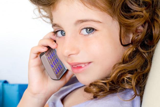 Menina de olhos azuis criança falando celular Foto Premium