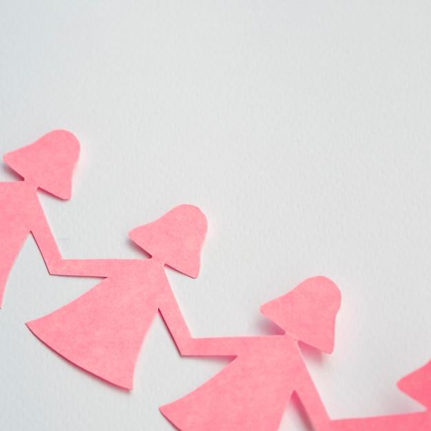 Menina de papel rosa de vista superior, de mãos dadas Foto gratuita