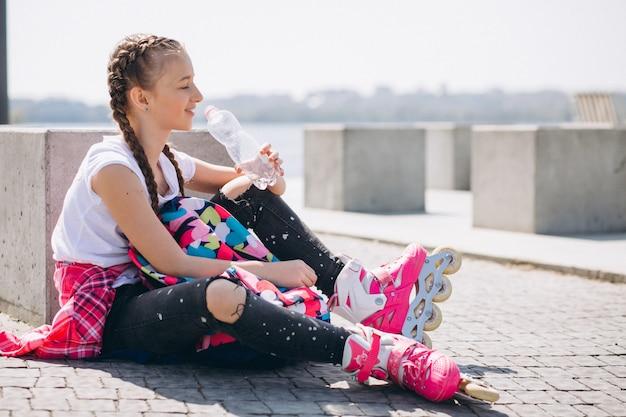Menina de patins e água potável Foto gratuita