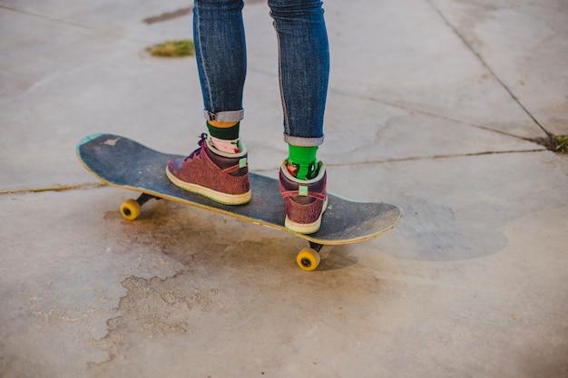 Menina de pé no skate para fora Foto gratuita