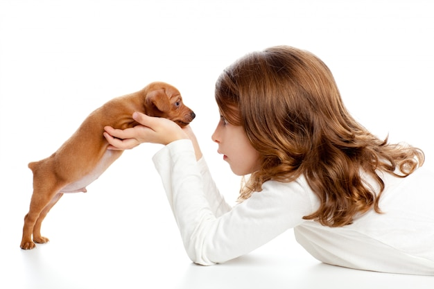 Menina de perfil morena com cachorro mini pinscher de cachorro Foto Premium