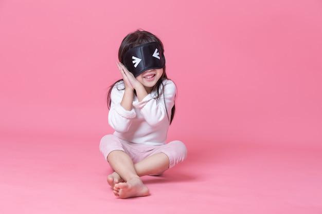 Menina de pijama branco e máscara preta, sentado no quarto rosa na hora de dormir. Foto Premium