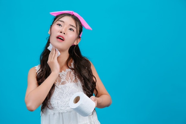 Menina de pijama branco usando papel de seda no rosto em um azul. Foto gratuita