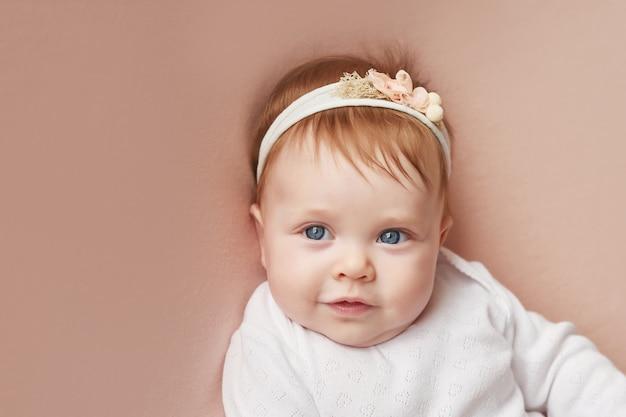 Menina de quatro meses encontra-se em uma parede rosa clara Foto Premium