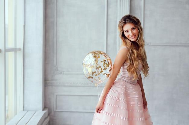 Menina de sorriso bonita da mola em um vestido cor-de-rosa com balões Foto Premium