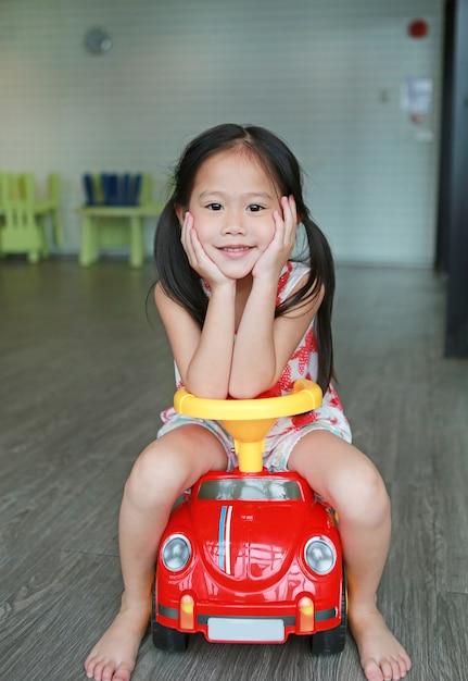 Menina de sorriso da criança pequena que monta em um carro pequeno na sala de jogos. Foto Premium