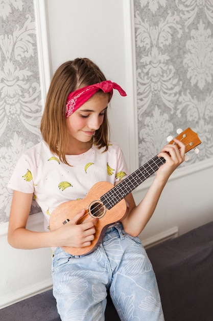 Menina de sorriso que joga o ukulele em casa Foto gratuita