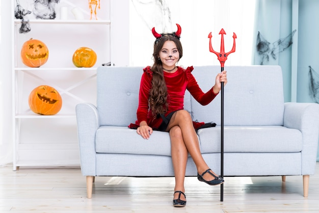Menina de tiro completo com chifres de diabo e tridente de halloween Foto gratuita