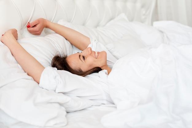 Menina de tiro médio, acordando na cama confortável Foto gratuita