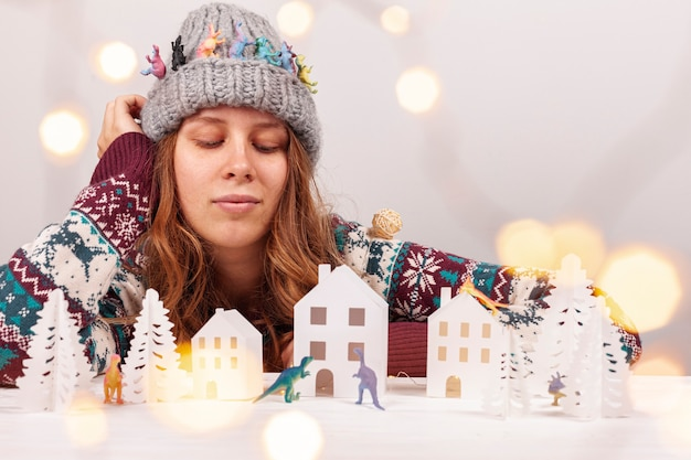 Menina de tiro médio com chapéu e papel cidade Foto gratuita