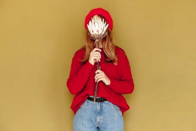 Menina de tiro médio com flor e fundo amarelo Foto gratuita