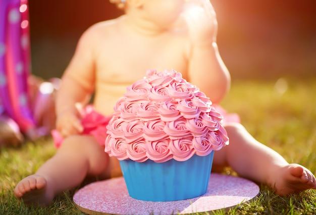 Menina de um ano comendo seu primeiro bolo Foto Premium