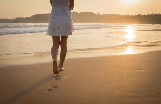 Menina de vestido branco caminhando ao longo da praia do oceano. vista das pernas e pés descalços. Foto Premium