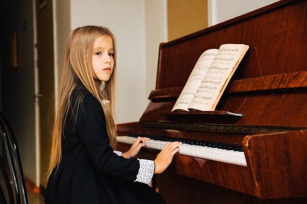 Menina de vestido preto aprende a tocar piano. a criança toca um instrumento musical. colegial, olhando para o lado. Foto Premium