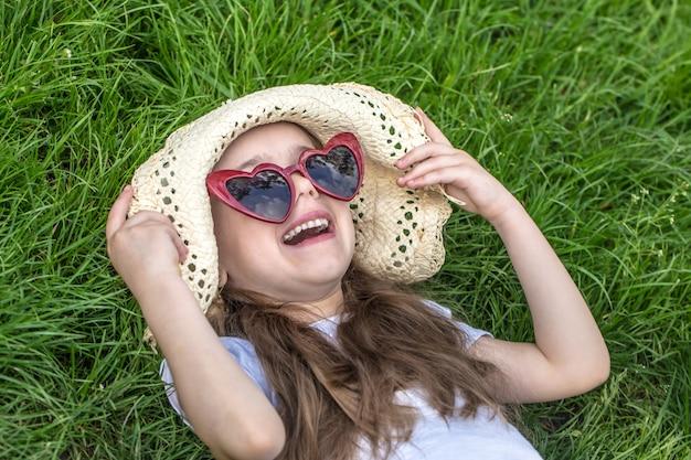 Menina deitada na grama. horário de verão e dia de sol Foto gratuita