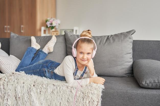 Menina deitada no sofá em fones de ouvido, ouvindo música com seu smarthphone Foto Premium