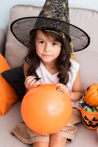 Menina desenhando um balão de halloween Foto gratuita