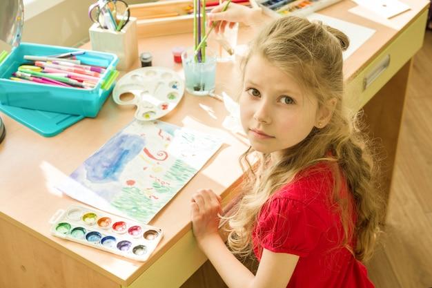 Menina desenho aquarela na mesa em casa Foto Premium