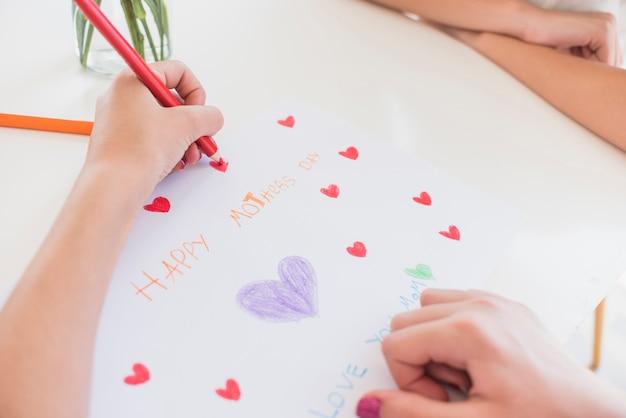 Menina desenho corações vermelhos em papel com inscrição feliz dia das mães Foto gratuita