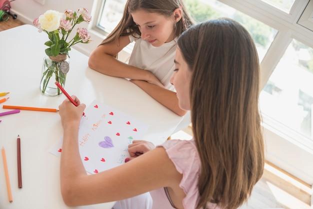 Menina desenho corações vermelhos em papel Foto gratuita