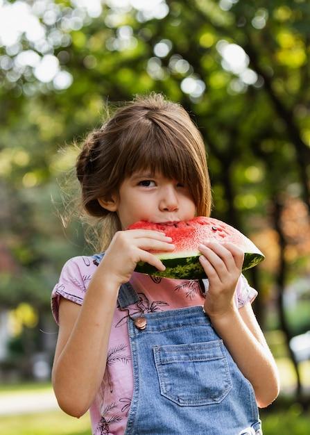 Menina, desfrutando de melancia ao ar livre Foto gratuita