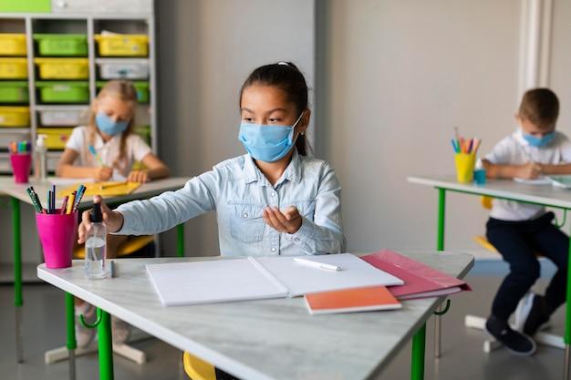 Menina desinfetando na sala de aula Foto gratuita
