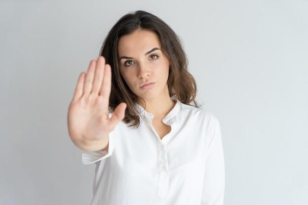 Menina determinada séria que mostra o sinal de parada. Foto gratuita