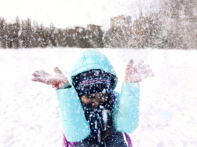 Menina do adolescente no divertimento exterior do inverno e na neve de jogo. Foto Premium