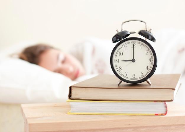 Menina do adolescente que dorme em uma cama branca. despertador em primeiro plano em uma pilha de livros Foto Premium