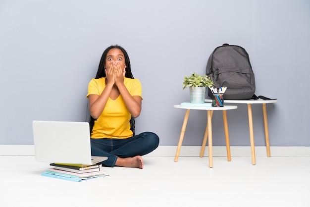 Menina do estudante do adolescente do americano africano com cabelo trançado longo que senta-se no assoalho com expressão facial da surpresa Foto Premium