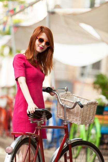 Menina do redhead com a bicicleta em ao ar livre, cidade. Foto Premium