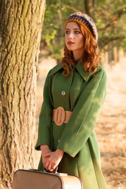 Menina do ruivo com a mala de viagem na aleia da árvore. Foto Premium