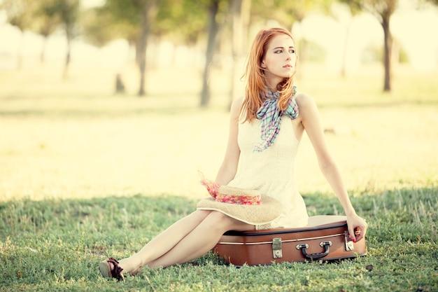 Menina do ruivo que senta-se no saco em ao ar livre. Foto Premium