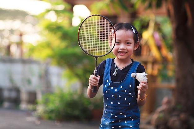 Menina do sorriso que joga o badminton em casa. Foto Premium