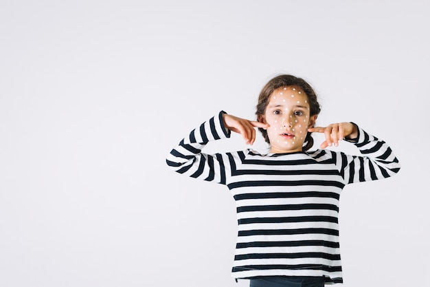 Menina doente, apontando para as bochechas Foto gratuita