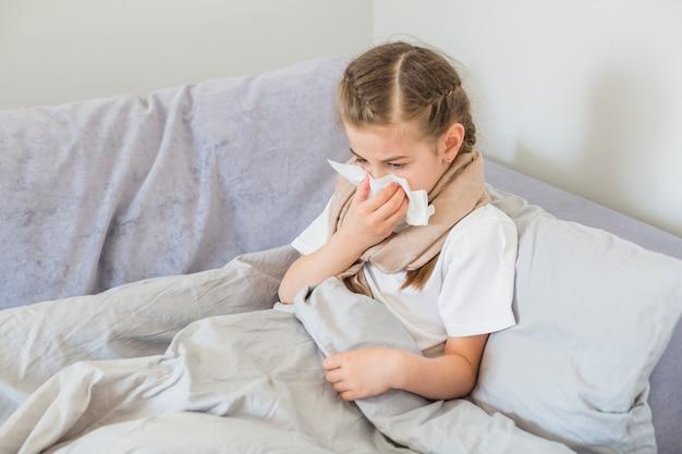Menina doente assoando o nariz Foto gratuita