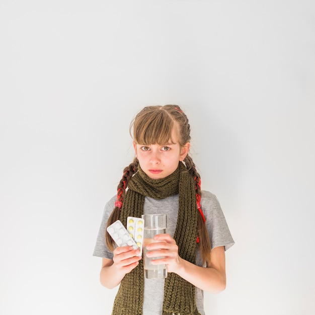 Menina doente com comprimidos Foto gratuita