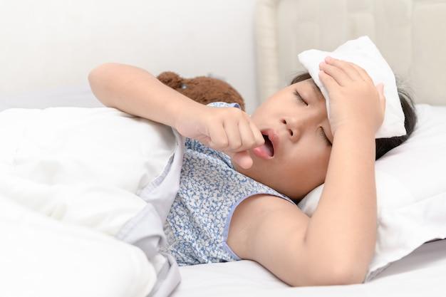Menina doente está tossindo e dor de garganta, deitada na cama Foto Premium