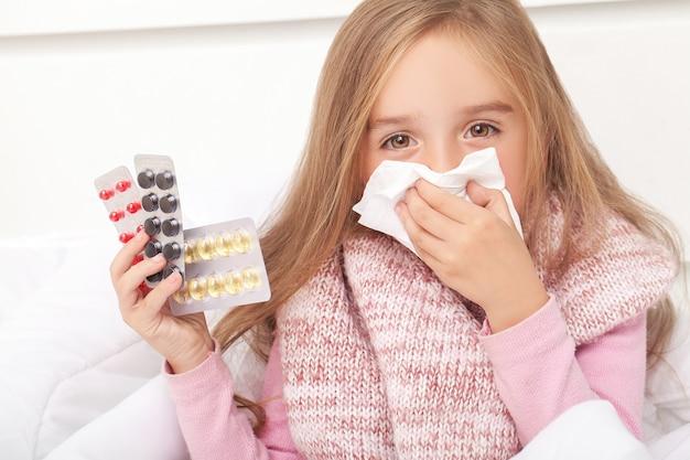 Menina doente na cama espirros no lenço no quarto Foto Premium