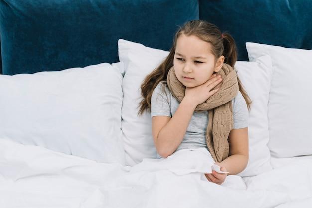 Menina doente sentado na cama com cachecol em volta do pescoço, sofrendo de pescoço dolorido Foto gratuita
