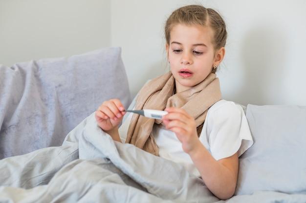 Menina doente usando termômetro Foto gratuita