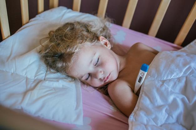 Menina dormindo em um travesseiro na cama com o termômetro Foto Premium