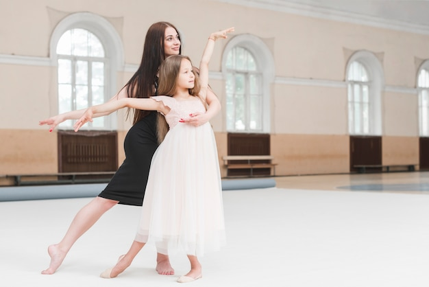 Menina e bailarina professora dançando juntos no estúdio de dança Foto gratuita